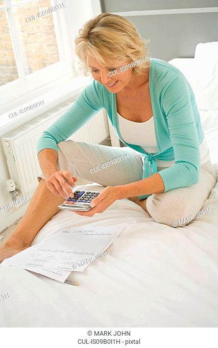 Mature woman sitting up on bed using calculator