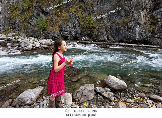 Young girl blowing bubbles along the Little Susitna river near Hatcher Pass, Southcentral Alaska, autumn