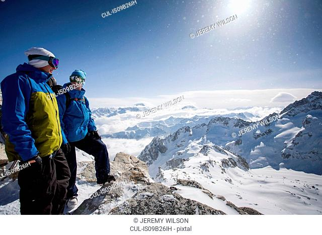 Two male snowboarders looking out over snow-covered landscape, Trient, Swiss Alps, Switzerland