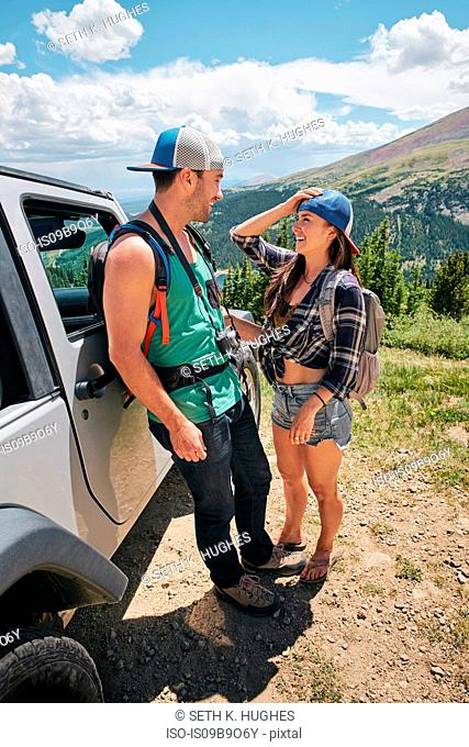 Road trip couple leaning against off road vehicle in Rocky mountains, Breckenridge, Colorado, USA