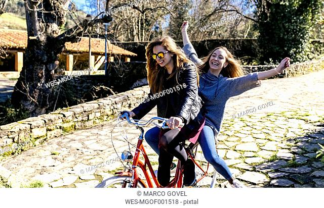 Two playful young women riding bicycle