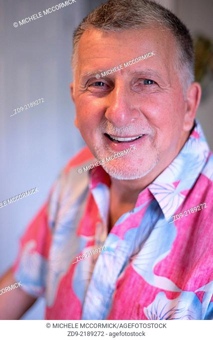 A happy gray-haired man in a flowered shirt