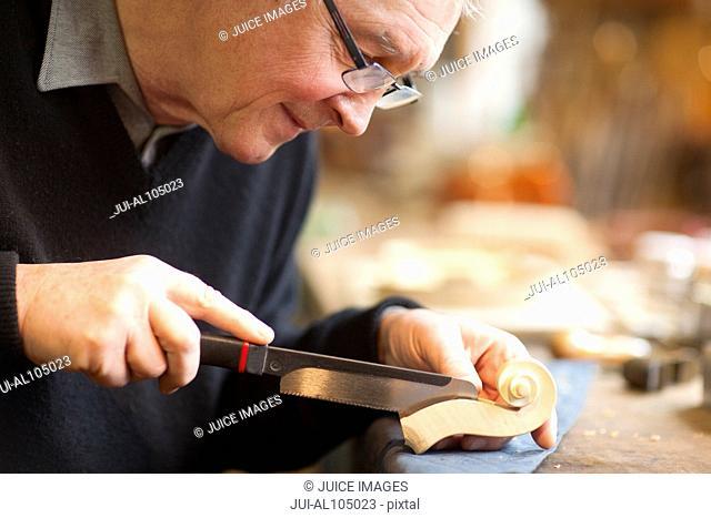 Violin maker working on violin in workshop