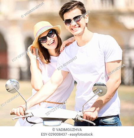 Beautiful young couple smiling to camera while woman sitting on scooter. Romantic journey