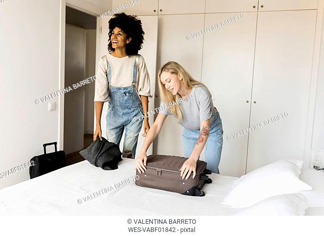 Two smiling women with baggage arriving in accomodation