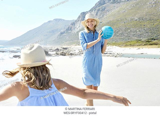 Mother and daughter playing ball an the beach
