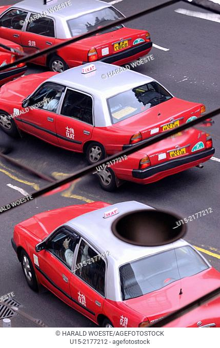 Hong Kong, China, Asia. Mirror image of typical red and silver Hong Kong Taxis