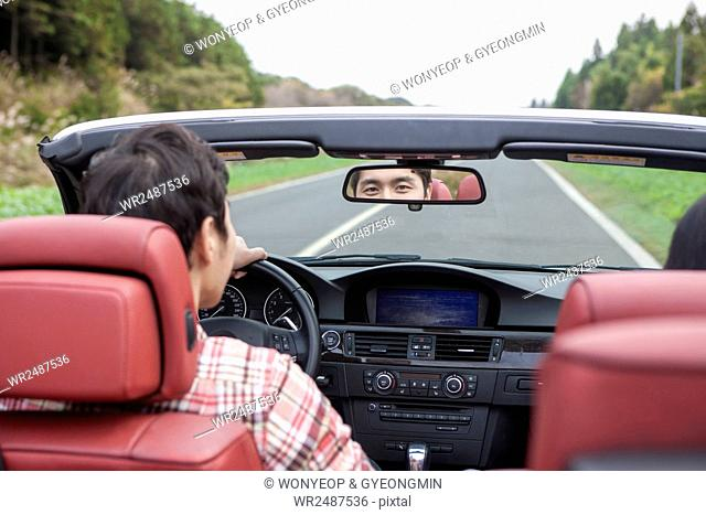 Back portrait of young man driving a car