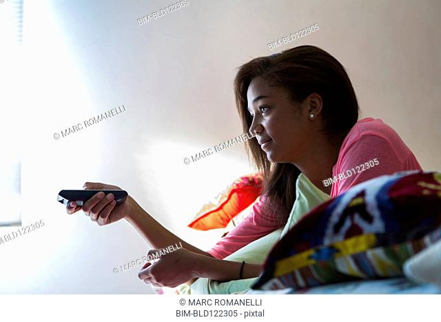 Mixed race teenage girl watching television on bed