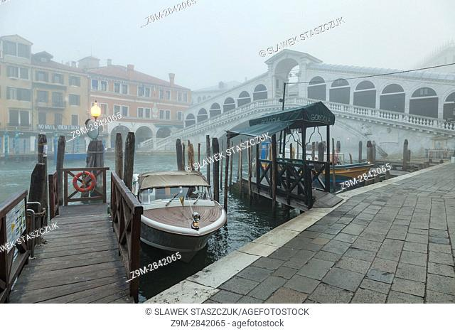 Foggy morning in the sestier of San Marco, Venice, Italy. . Rialto bridge in the distance