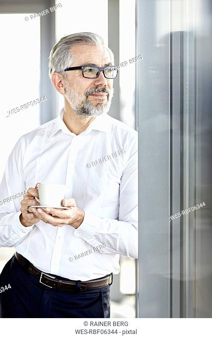 Businessman with cup of coffee looking out of window
