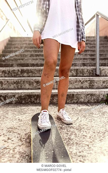 Legs of young woman with skateboard
