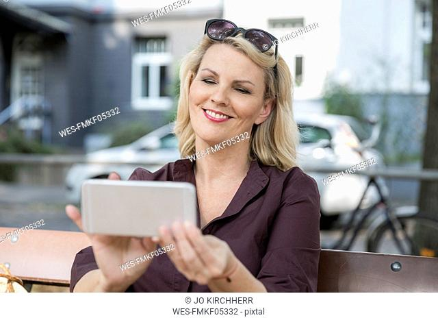 Portrait of smiling blond mature woman using smartphone outdoors