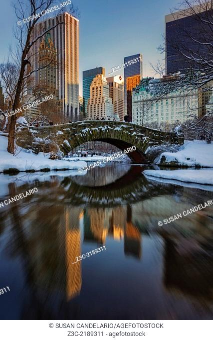 Gapstow Bridge reflected in the pond during sunset at Central Park in New York City after a snow storm. The Plaza Hotel and other New York City skyscrapers can...