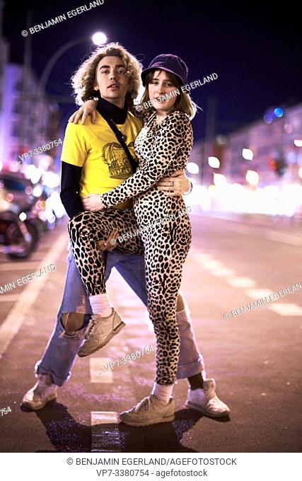 man and woman entangled, standing at street at night, nightlife in Berlin, Germany