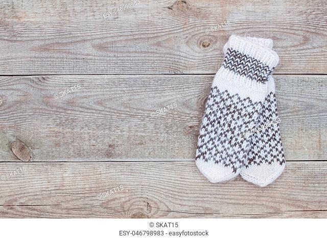 Knitted white wool mittens on old wooden background with copy space