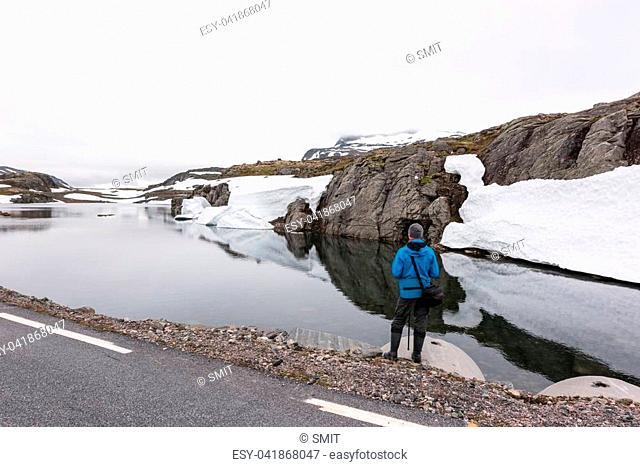Photographer taking photo of typical norwegian landscape with snowy mountains and clear lake near the famous Aurlandsvegen mountain road, Aurland, Norway