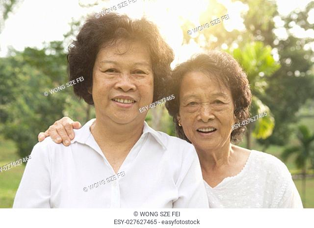 Portrait of healthy happy Asian seniors mother and daughter at outdoor nature park, morning beautiful sunlight background