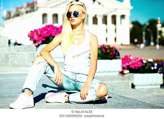 High fashion look.glamor stylish beautiful young blond model girl teenager in summer bright casual hipster clothes with skateboard behind blue sky in the street