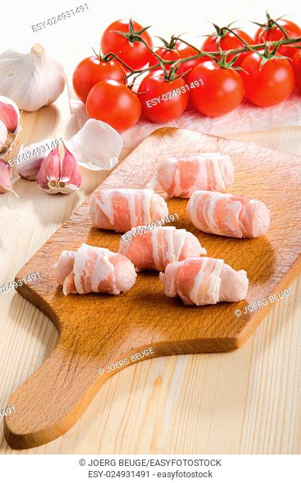 raw party sausages wrapped with bacon on wooden board
