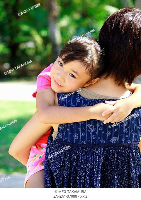 Rear view of a young woman carrying her daughter