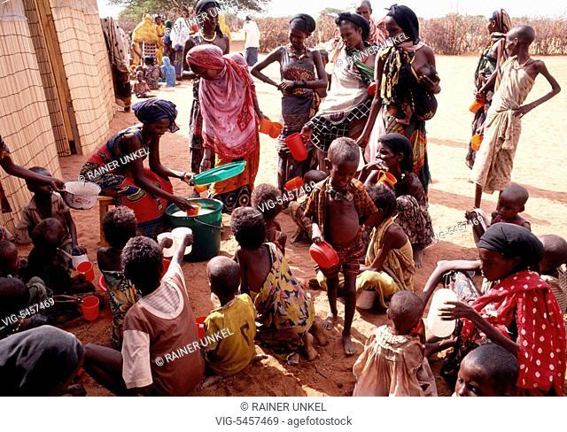 KENYA, WAJIR, 12.06.1992, KEN , KENYA : A local worker of a NGO is distributing milk to the needy people in a feeding centre in Wajir , June 1992 - Wajir