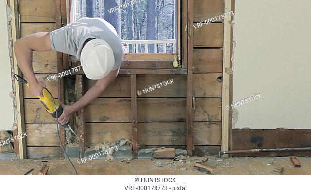 Carpenter using reciprocating saw to cut wall studs through old window