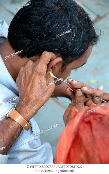 Delhi, India: ear cleaning along a sidewalk