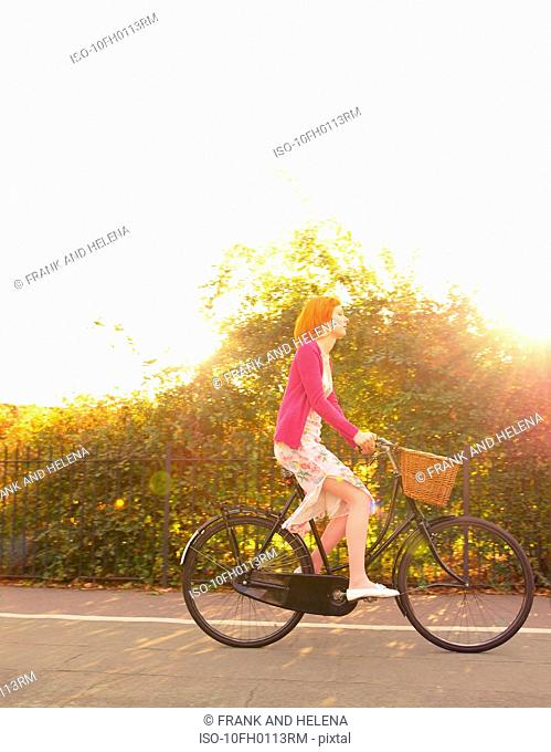Young redhead woman cycling in park