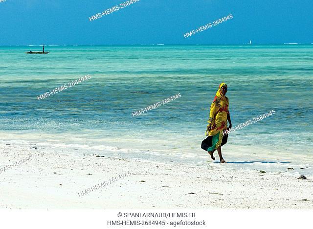 Tanzania, Zanzibar, Jambiani, young veiled woman walking on a sandy beach