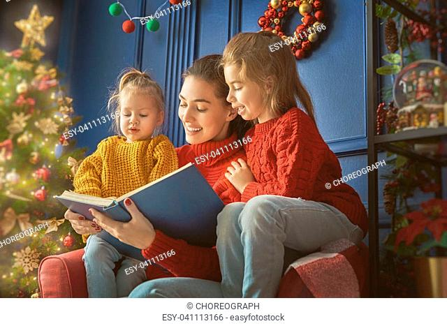 Merry Christmas! Pretty young mother reading a book to her daughters near Christmas tree