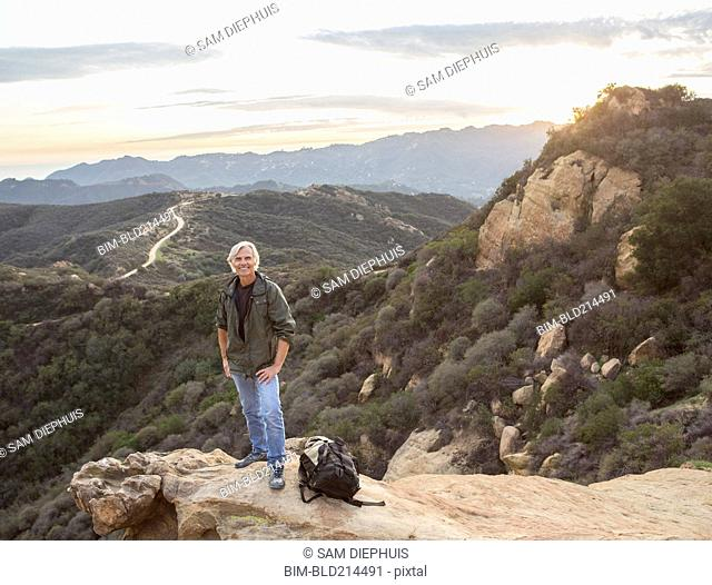 Older Caucasian man standing on rocky hilltop