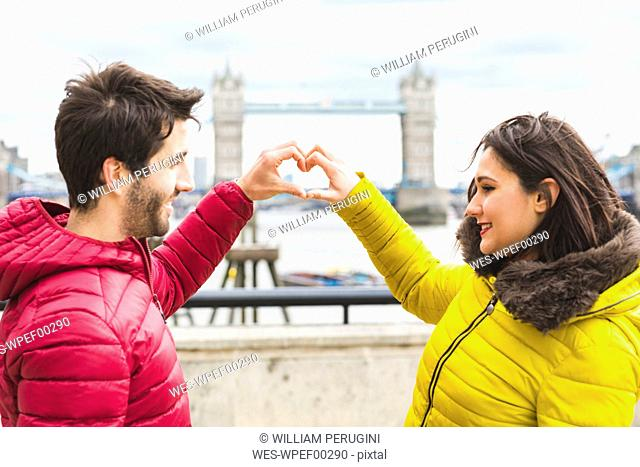 UK, London, young couple standing on bridge over the Thames forming heart with their hands