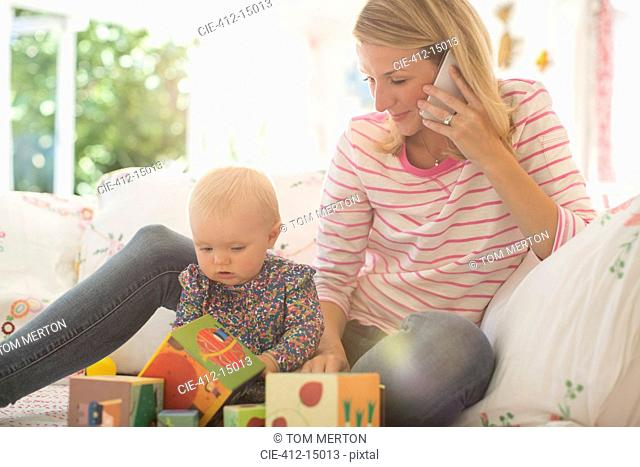 Mother with baby girl talking on cell phone