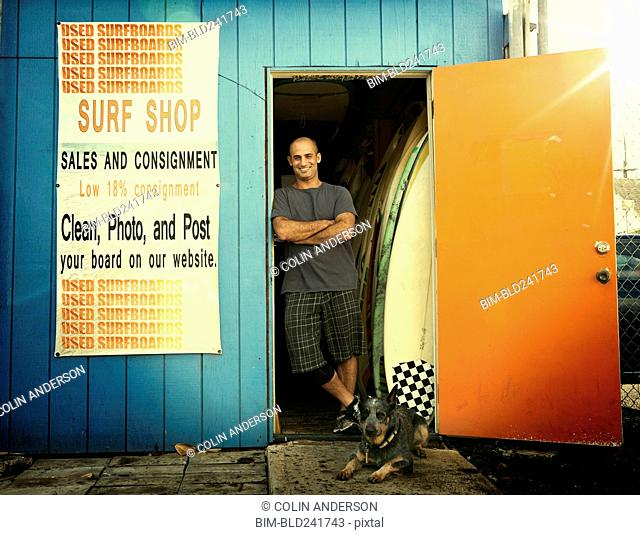 Caucasian man leaning in doorway of surfboard shop