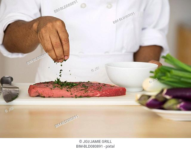 Mixed race chef seasoning steak
