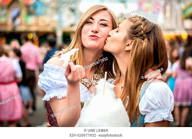 Two young women in traditional Bavarian clothes, dirndl or tracht, kissing with cotton candy floss at the Oktoberfest
