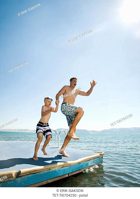 Father and son 4-5 jumping into lake caught
