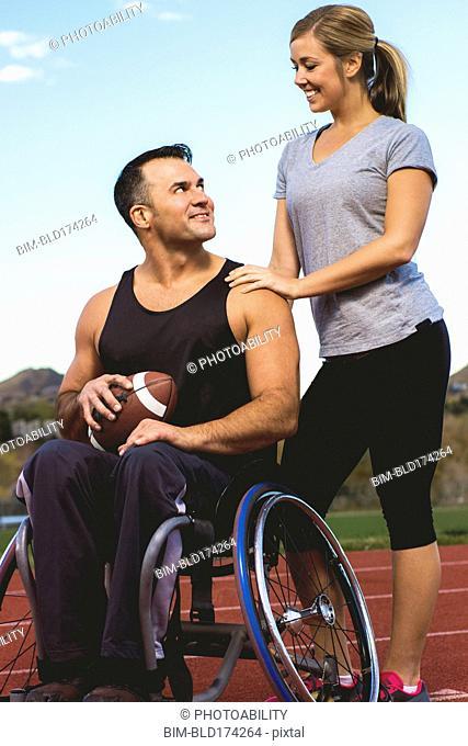 Paraplegic athlete in wheelchair with girlfriend