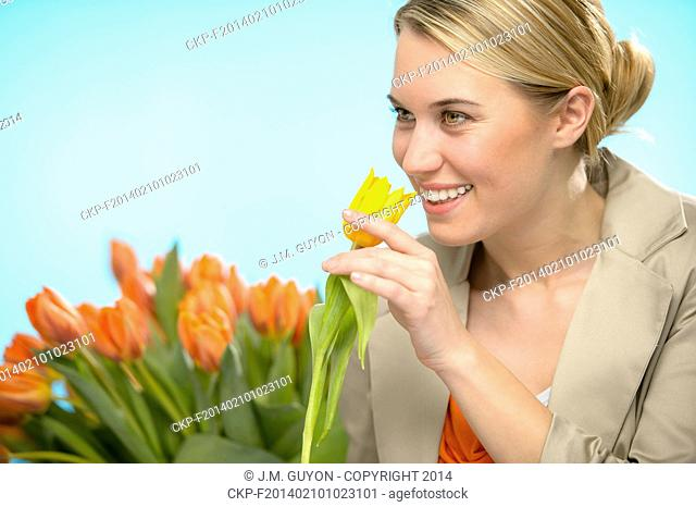Woman smelling one yellow tulip spring flowers smiling