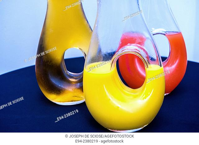 3 glass pitchers filled with fruit juice
