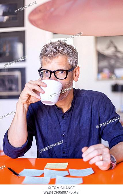 Portrait of mature man at table with notepads drinking coffee