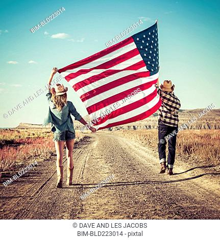 Hispanic couple walking in desert carrying American flag