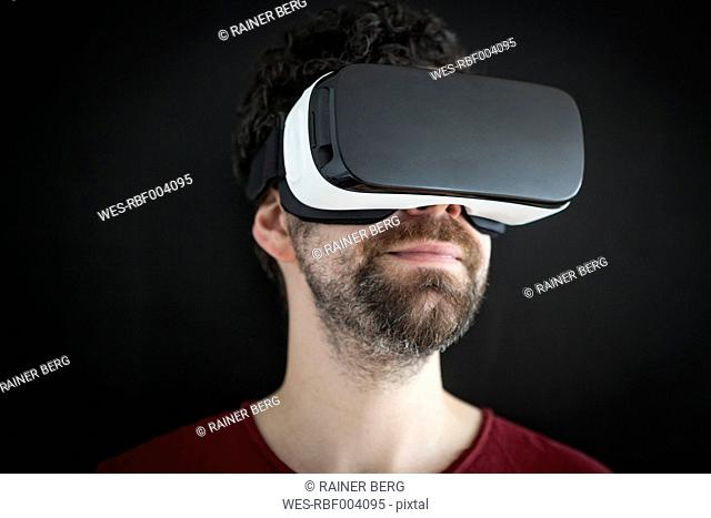 Smiling man wearing Virtual Reality Glasses in front of black background