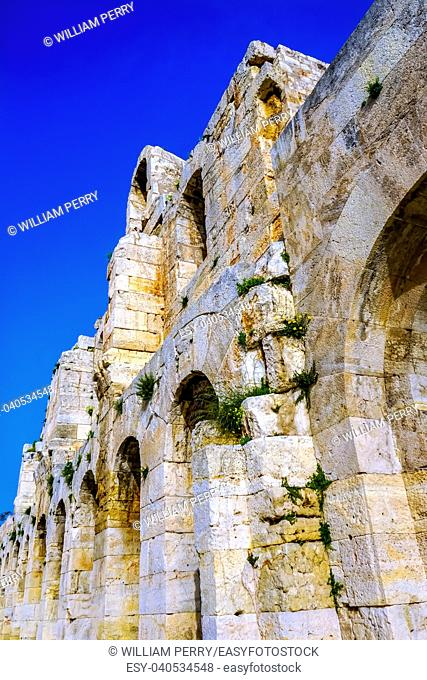 Odeon of Herodes Attiacus Yellow Flowers Acropolis Athens Greece. Stone Theater base of Acropolis. Built 161 AD. Renovated 1950, used as concert stage today