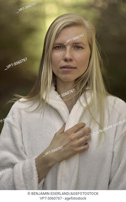 Portrait of woman in nature wearing a white bathrobe. Waakirchen, Bavaria, Germany
