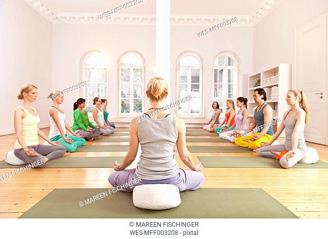 Group of people in yoga studio sitting in Lotus pose in front of instructor