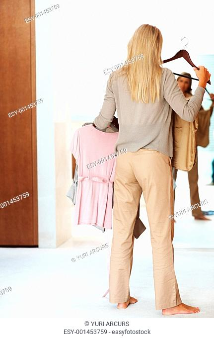 Rear view of a mature woman trying clothes in front of a mirror