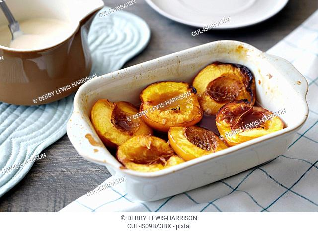 Baked nectarines in white dish, close-up