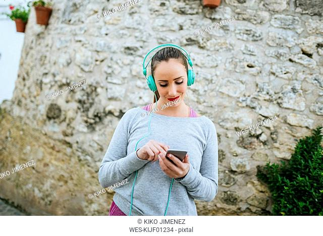 Young woman with headphones sending message with mobile phone